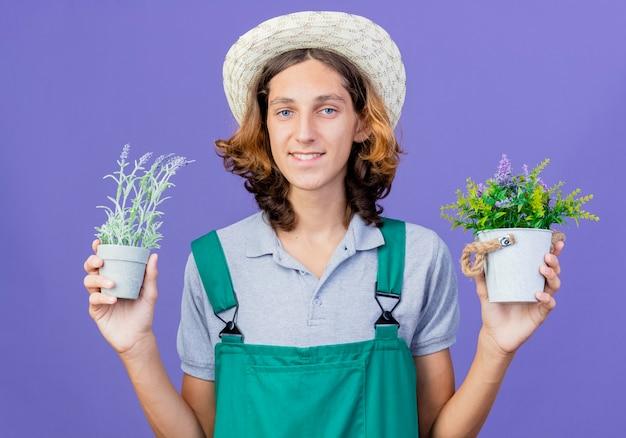 Jovem jardineiro vestindo macacão e chapéu segurando vasos de plantas sorrindo