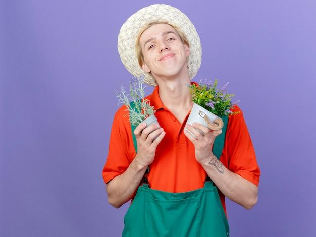 Jovem jardineiro vestindo macacão e chapéu segurando vasos de plantas
