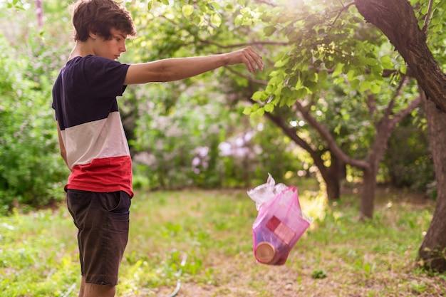 Jovem joga o pacote de plástico com o lixo na zona do parque natural, poluição ambiental