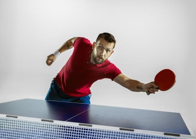 Jovem joga tênis de mesa na parede branca.