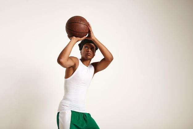 Jovem jogador afro-americano em forma focada, com roupa de basquete verde e branco, jogando uma bola de basquete vintage isolada no branco