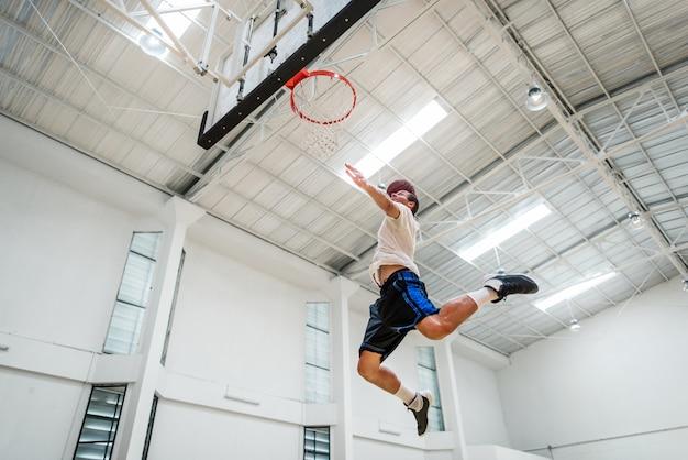 Jovem jogador de basquete arremessa