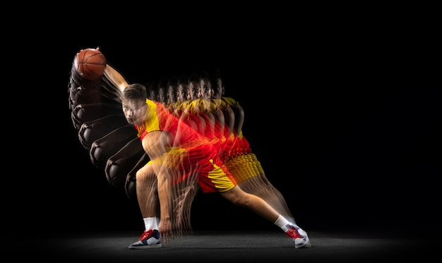 Jovem jogador de basquete caucasiano em movimento e ação em luz mista em fundo escuro.