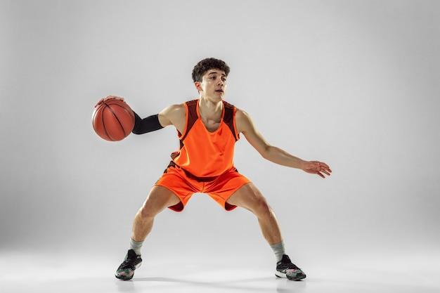 Jovem jogador de basquete da equipe vestindo treinamento esportivo, praticando em ação, movimento em execução isolado na parede branca