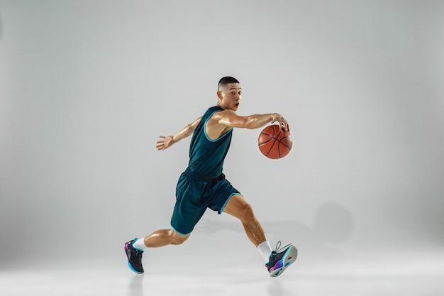 Jovem jogador de basquete da equipe vestindo treinamento sportwear, praticando em ação, movimento em execução isolado na parede branca. conceito de esporte, movimento, energia e estilo de vida dinâmico e saudável.