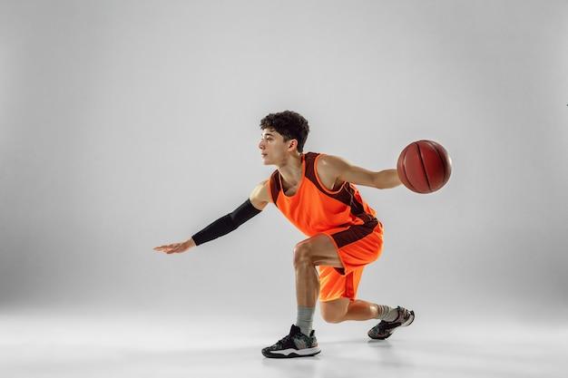 Jovem jogador de basquete da equipe vestindo treinamento sportwear, praticando em ação, movimento em execução isolado no fundo branco.