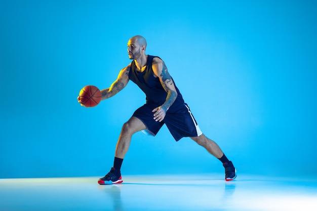 Jovem jogador de basquete do time vestindo roupas esportivas, treinando em ação, isolado na parede azul com luz de néon