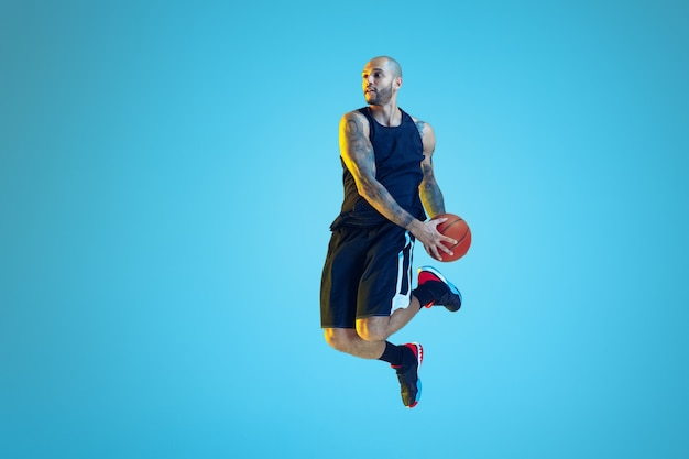 Jovem jogador de basquete do time vestindo roupas esportivas, treinando em ação, movimento na parede azul com luz de néon