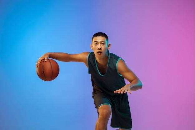 Jovem jogador de basquete em movimento no fundo gradiente do estúdio sob luz de néon
