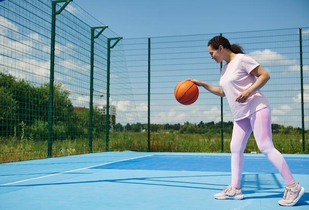Jovem jogador de basquete jogando uma bola de basquete na quadra ao ar livre