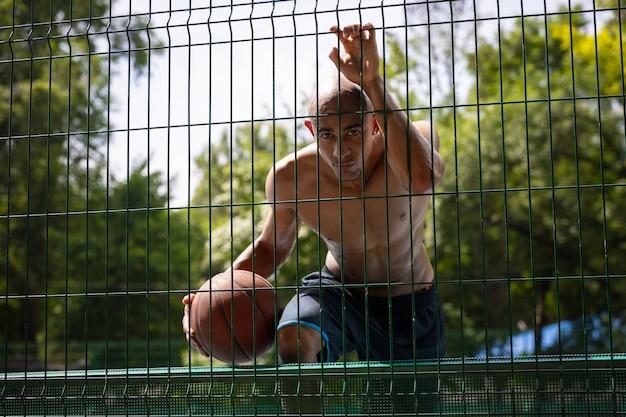 Jovem jogador de basquete masculino jogando na quadra de esportes pública ou palyground ao ar livre