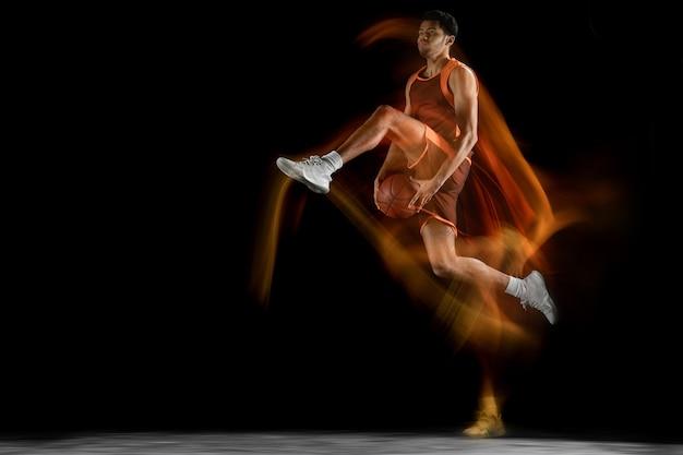 Jovem jogador de basquete muscular árabe em ação, movimento isolado no preto