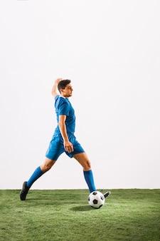 Jovem, jogador de futebol, cruzando bola