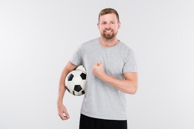 Jovem jogador de futebol de sucesso em roupas esportivas segurando uma bola e mostrando sua força na frente da câmera, isolado