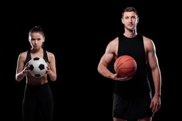Jovem jogador de futebol e basquete musculoso segurando bolas em pé