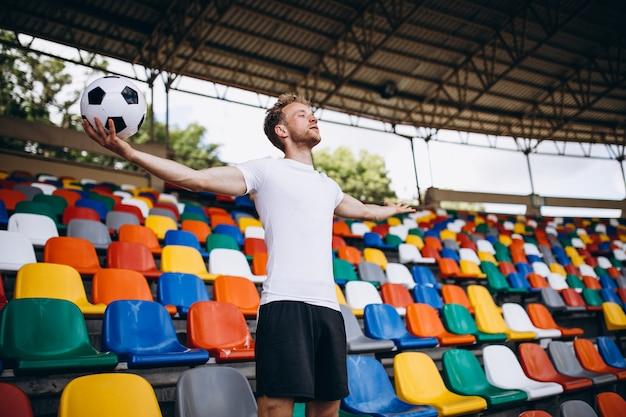Jovem jogador de futebol em tribunas assistindo o jogo