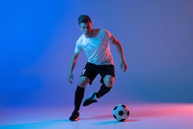 Jovem jogador de futebol masculino treinando isolado em uma parede gradiente
