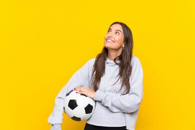 Jovem, jogador de futebol, mulher olha, cima, enquanto, sorrindo