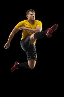 Jovem jogador de futebol treinando isolado na parede preta