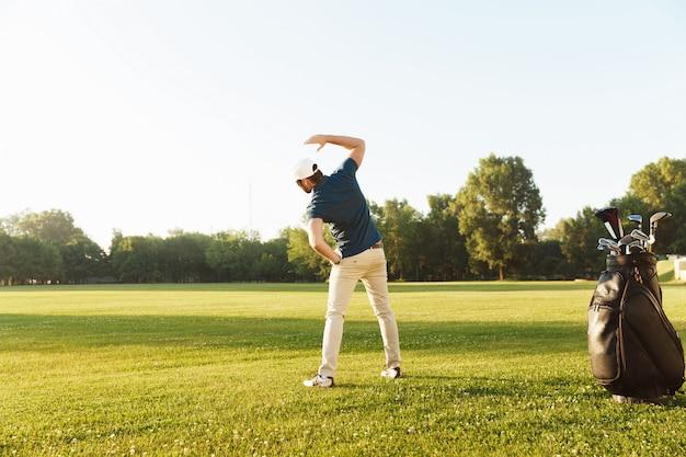 Jovem jogador de golfe esticando os músculos antes de iniciar o jogo