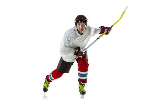 Jovem jogador de hóquei com o taco na quadra de gelo e fundo branco.