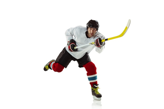 Jovem jogador de hóquei com o taco na quadra de gelo e parede branca. esportista usando equipamento e praticando capacete