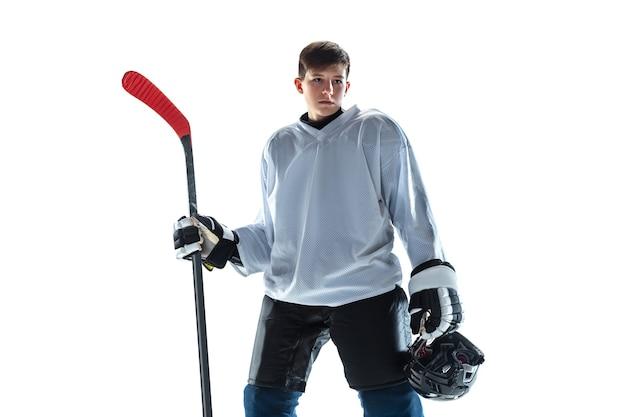 Jovem jogador de hóquei com o taco na quadra de gelo