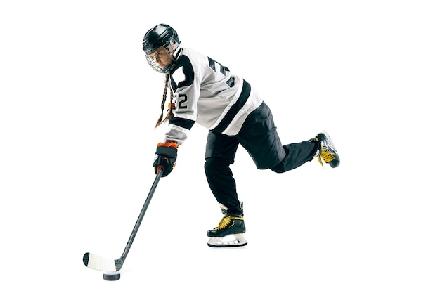 Jovem jogador de hóquei feminino com o taco isolado no fundo branco. desportista em ação, usando equipamentos de ataque para o gol ou pontuação. conceito de esporte, estilo de vida saudável, movimento, movimento.