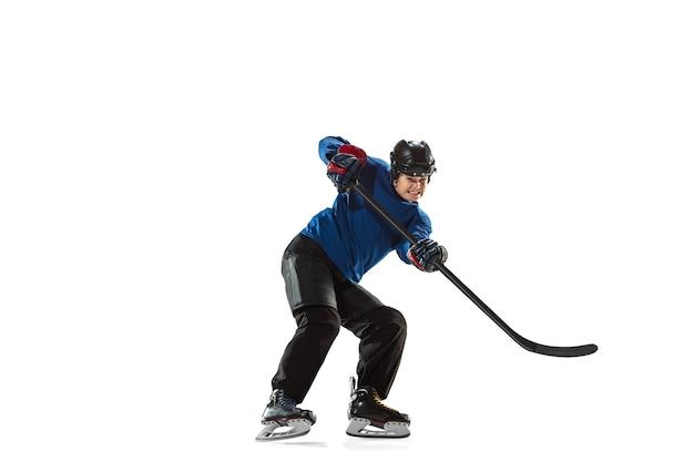 Jovem jogador de hóquei feminino com o taco na quadra de gelo e fundo branco. desportista usando equipamento e treinamento de capacete. conceito de esporte, estilo de vida saudável, movimento, ação, emoções humanas.