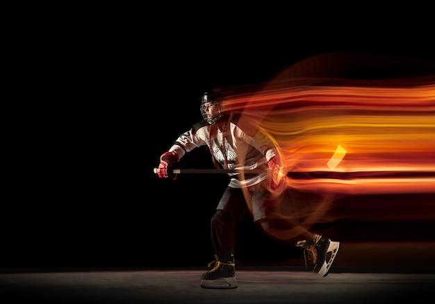 Jovem jogador de hóquei feminino com o taco no fundo preto e a luz de néon. desportista usando equipamento e treino de capacete. conceito de esporte, estilo de vida saudável, movimento, movimento, ação.