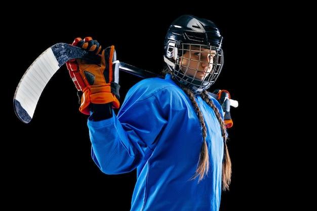 Jovem jogador de hóquei feminino isolado no fundo preto. desportista usando equipamento e capacete em pé com o taco. conceito de esporte, estilo de vida saudável, movimento, movimento, ação.