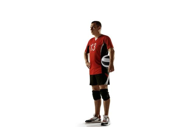Jovem jogador de voleibol caucasiano aplacando na parede branca. esportista masculino posando confiante com a bola, preparado para a vitória. esporte, estilo de vida saudável, atividade, conceito de movimento. copyspace.