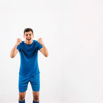 Jovem, jogador futebol, celebrando, vitória