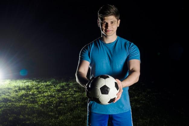 Jovem, jogador futebol, segurando bola