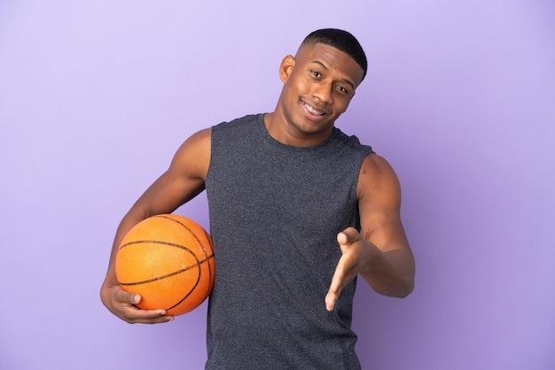 Jovem jogador latino de basquete isolado na parede roxa apertando as mãos para fechar um bom negócio