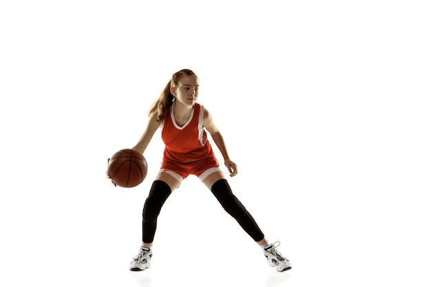Jovem jogadora de basquete em ação, movimento em execução isolado na parede branca