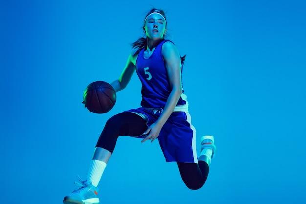 Jovem jogadora de basquete feminina, branca, isolada no fundo azul do estúdio, sob luz de néon