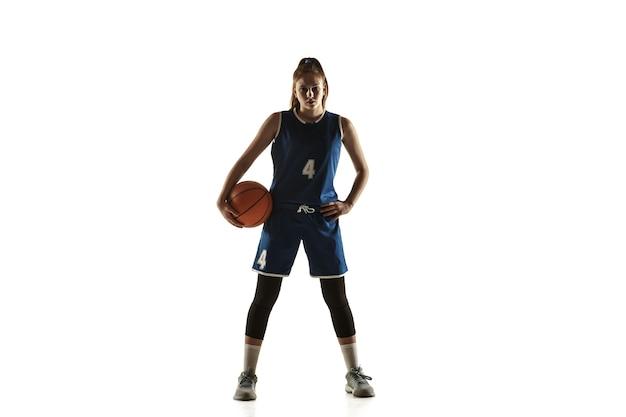 Jovem jogadora de basquete feminino caucasiano da equipe posando confiante com uma bola isolada no fundo branco.