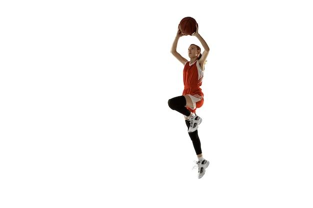 Jovem jogadora de basquete feminino caucasiano em ação, movimento em salto isolado no fundo branco. garota esportiva redhair. conceito de esporte, movimento, energia e estilo de vida dinâmico e saudável. treinamento.
