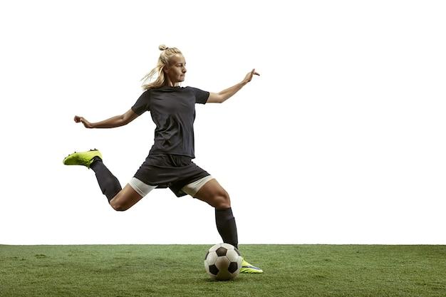 Jovem jogadora de futebol ou futebol americano com cabelo comprido em roupas esportivas e botas, chutando bola
