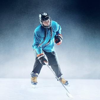 Jovem jogadora de hóquei com o taco na quadra de gelo e fundo azul