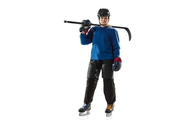 Jovem jogadora de hóquei com o taco na quadra de gelo e fundo branco