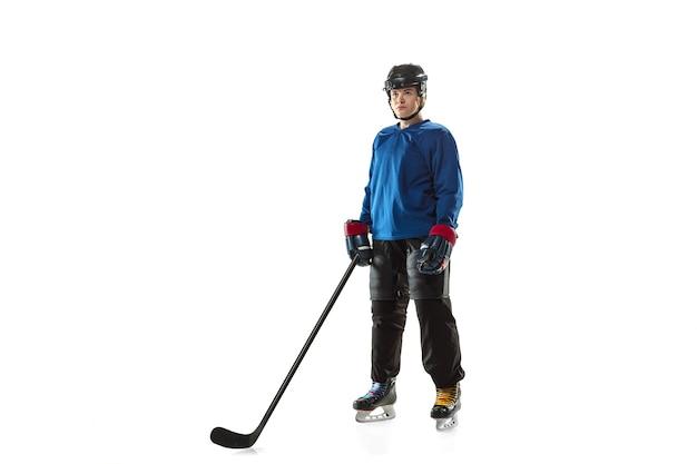 Jovem jogadora de hóquei com o taco na quadra de gelo e parede branca