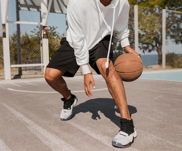 Jovem jogando basquete de frente