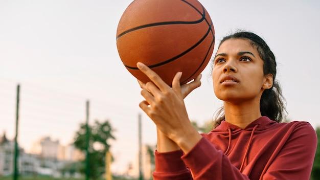 Jovem jogando basquete lá fora