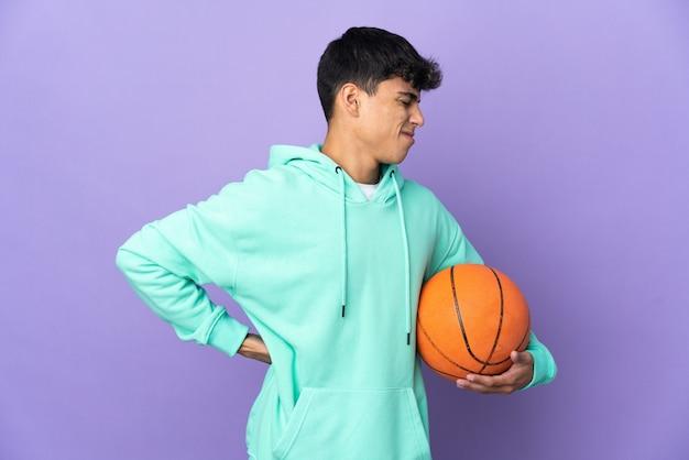 Jovem jogando basquete sobre o roxo, sofrendo de dor nas costas por ter feito um esforço