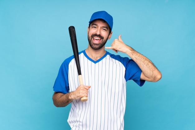 Jovem jogando beisebol fazendo gesto de telefone.