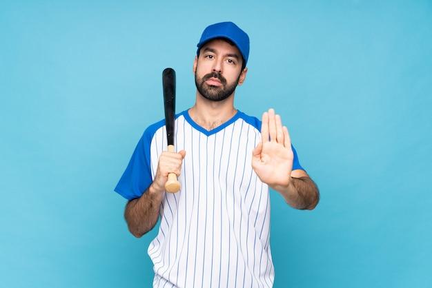 Jovem jogando beisebol, fazendo o gesto de parada