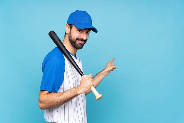 Jovem jogando beisebol isolado azul apontando para trás