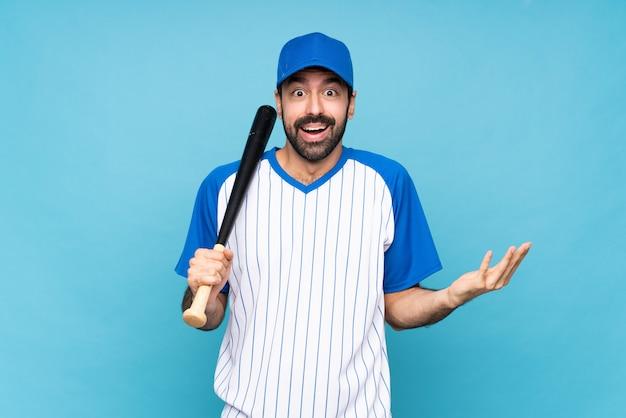 Jovem jogando beisebol sobre azul isolado com expressão facial chocado